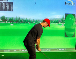 Player using the OptiGolf indoor golf simulator
